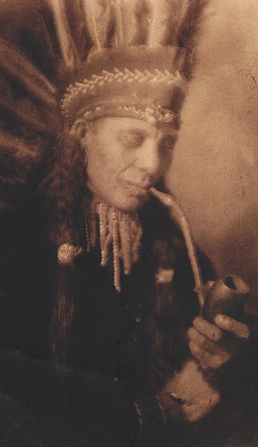 Ernest Jones with pipe and headdress